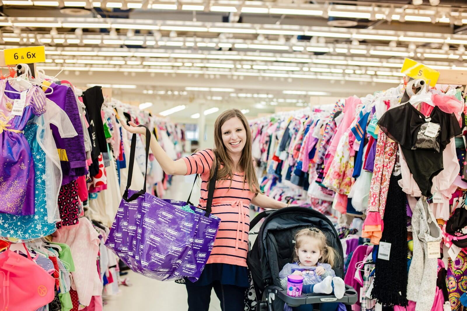 A Mom holds up her JBF shopping bag with her right hand while resting her left hand on her stroller with toddler daughter inside.